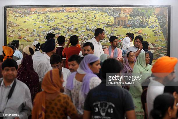 Indian visitors look at a painting depicting the Jallianwala Bagh massacre in Amritsar on April 12 2011 The Amritsar massacre also known as the...