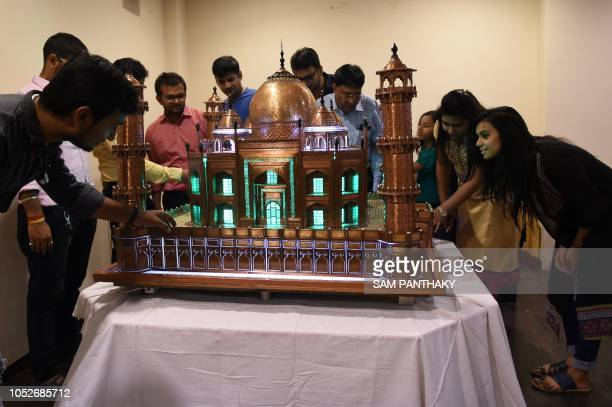 Indian visitors look at sculptor Dilipbhai Zinzuwadia's Taj Mahal model made with copper and acrylic in Ahmedabad on October 21 2018