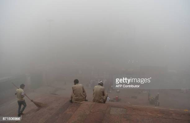 Indian visitors sit on the steps outside Jama Masjid amid heavy smog in the old quarters of New Delhi on November 8 2017 Delhi shut all primary...