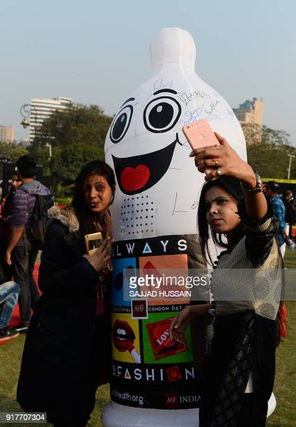Indian visitors take selfies with volunteers dressed as condoms during an event to mark International Condom Day in New Delhi on February 13, 2018....