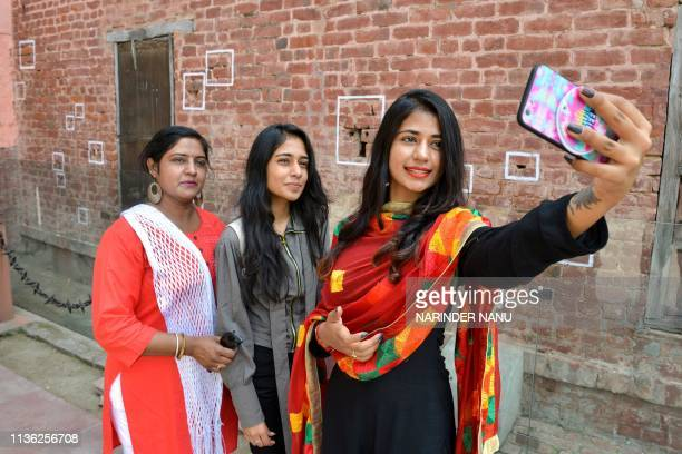 Indian visitors takes selfies with their mobile phone in front of bullet marks on a wall near the Jallianwala Bagh Martyrs' Memorial ahead of the...