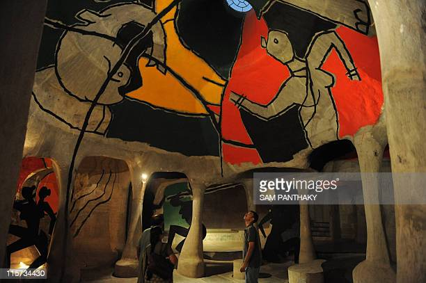 Indian visitors view the works of artist MF Husain at underground art gallery 'HussainDoshi Gufa' in Ahmedabad on June 9 2011 The gallery exhibits...