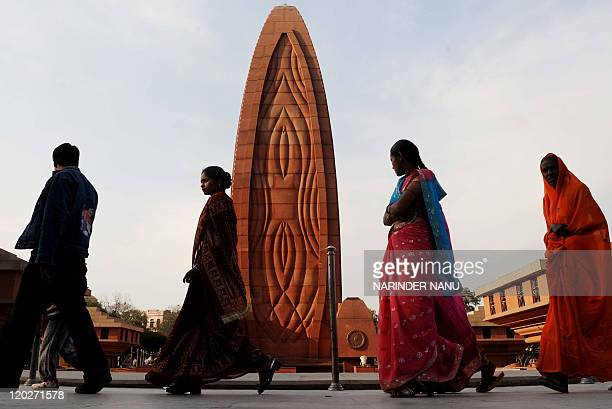 Indian visitors walke past the Flame of Liberty memorial at Jallianwala Bagh in Amritsar on February 4 2010 The Amritsar massacre also known as the...