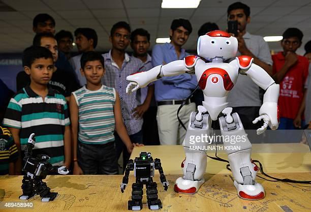Indian visitors watch autonomus humonoid robot 'NAO' dance during the ROBOFEST 2015 robotics exhibition in Bangalore on April 12 2015 AFP...