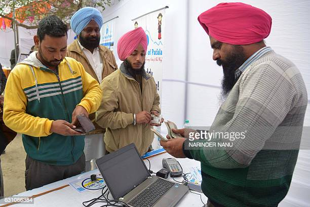 Indian visitors withdraw money from their bank accounts with an Aadhaar or Unique Identification card during a Digi Dhan Mela held to promote digital...