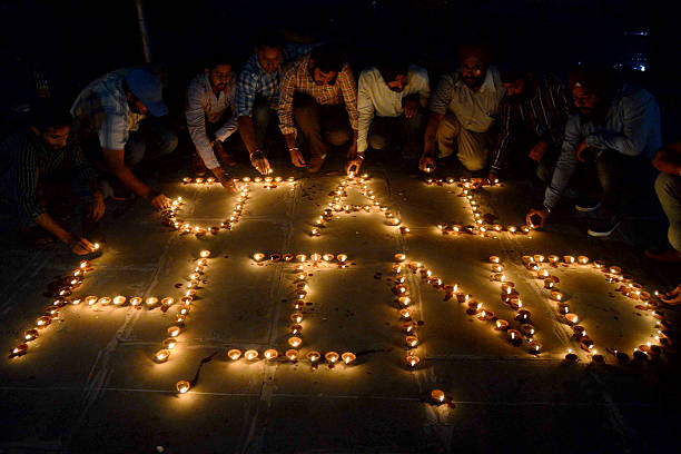 Indian volunteer light `diyas` or oil lamps in the shape of a `Jai Hind` victory to India to support the Indian Army during celebrations of Diwali...