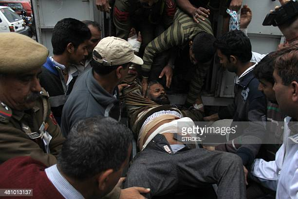Indian volunteers and medical staff help an injured resident from an ambulance towards the emergency ward of The Government Medical College Hospital...
