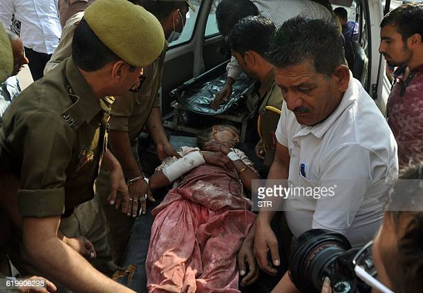 Indian volunteers and officials carry an injured villager into The Government Medical College Hospital in Jammu on November 1 after she was injured...