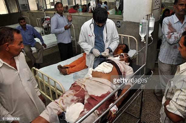 Indian volunteers and officials use a trolley to wheel injured villager Ashok Kumar into The Government Medical College Hospital in Jammu on November...
