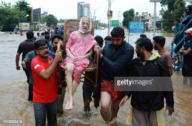 TOPSHOT Indian volunteers and rescue personal evacuate local residents in a residential area in Ernakulam district in the Indian state of Kerala on...