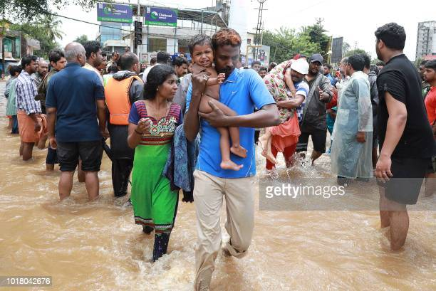 TOPSHOT Indian volunteers and rescue personal evacuate local residents in a residential area at Aluva in Ernakulam district in the Indian state of...