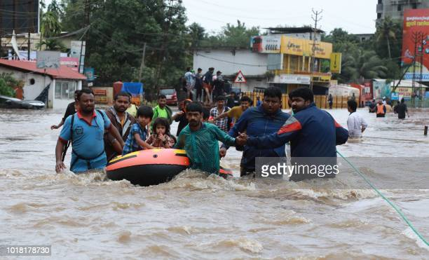TOPSHOT Indian volunteers and rescue personal evacuate local residents in a boat in a residential area at Aluva in Ernakulam district in the Indian...