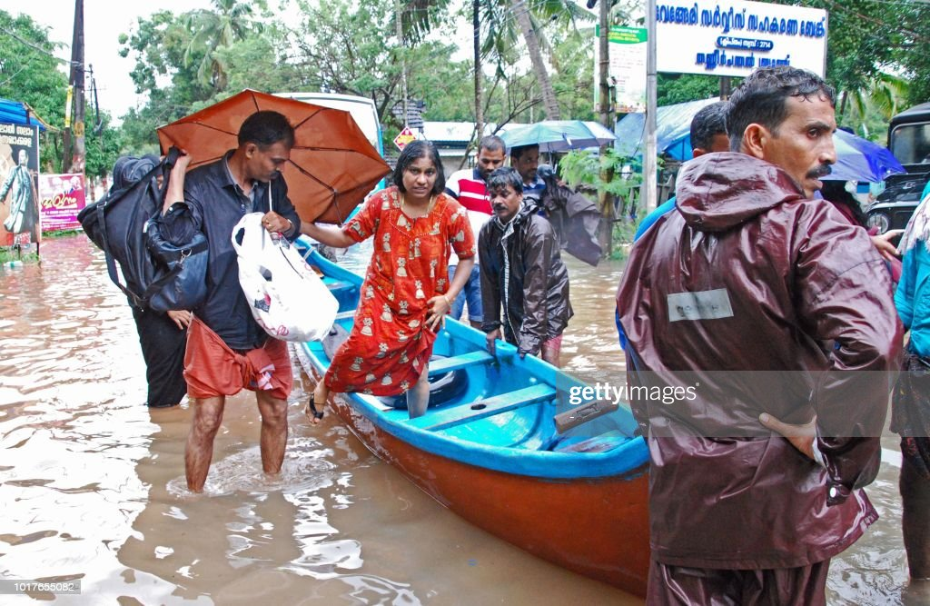 Indian volunteers and rescue personnel evacuate local residents in a boat in a residential area at Kozhikode, in the Indian state of Kerala, on August 16, 2018. - The death toll from floods in India's tourist hotspot of Kerala increased to 77 on August 16, as torrential rainfall threatened new areas, officials told AFP.