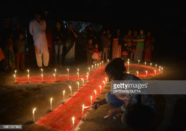Indian volunteers and sex workers light candles forming the shape of a ribbon as part of an awareness event on the occasion of World AIDS Day in...