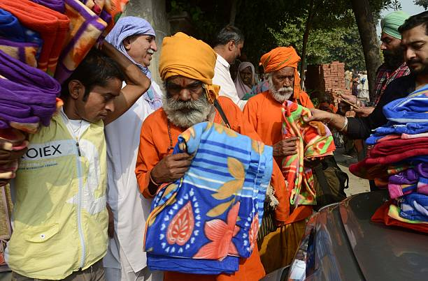 Indian volunteers distribute blankets to Sadhus during a Sadhu congregation following the Diwali Festival in Amritsar on October 31 2016 Thousands of.