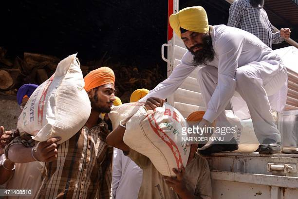 Indian volunteers from the Shiromani Gurdwara Prabhandhak Committee load relief materials onto a truck to be taken to Nepal near the Golden Temple in...