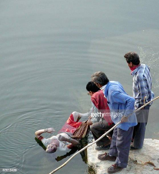 Indian volunteers pull the body of a victim of a water discharge out of the Narmada river 11 April 2005 outside the village of Dharaji in the Dewas...
