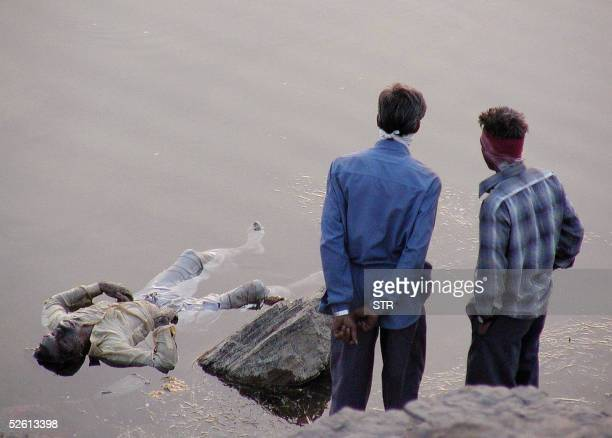 Indian volunteers stand on the edge of the Narmada river where the body of a victim of a water discharge floats 11 April 2005 outside the village of...