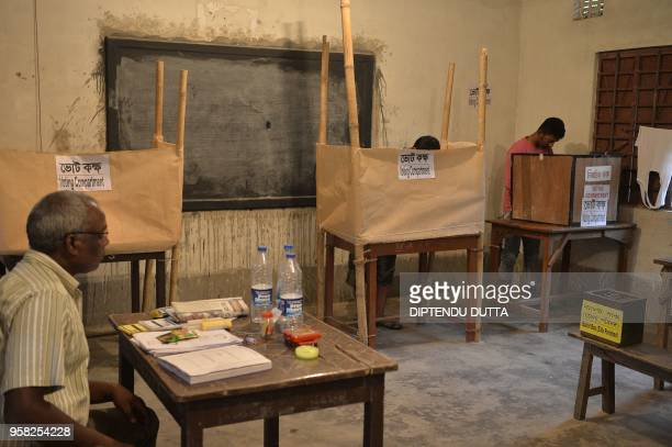 TOPSHOT Indian voters caste their votes at a polling station for Panchayet elections at Chopra village in West Bengal on May 14 2018 West Bengal...