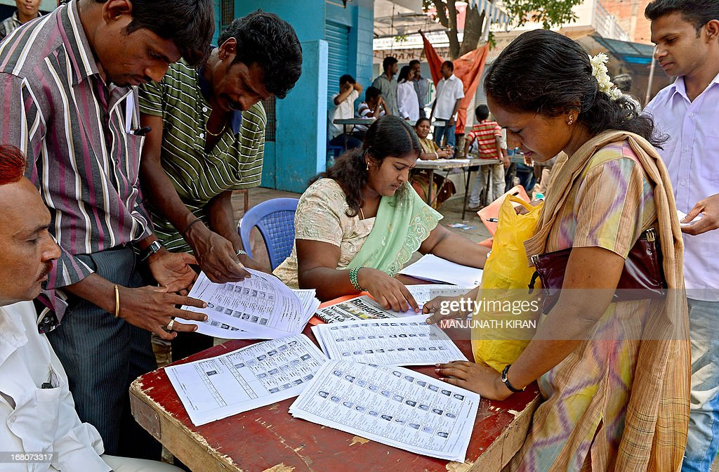 Indian voters check their names on a voters list near a polling booth during state Assembly elections in Bangalore on May 5, 2013. Polling began this morning for the Assembly polls in Karnataka state in which the Indian Congress Party has pulled out all the stops to return to power in a complex battle after more than an eight year long gap. AFP PHOTO/ Manjunath KIRAN