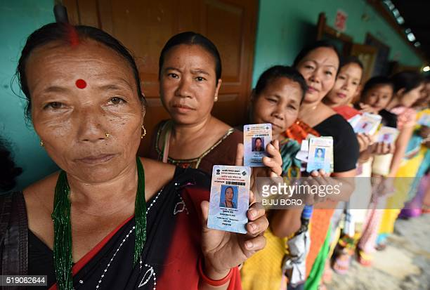 Indian voters pose for a photograph with their identity cards as they queue to cast their ballots in the state assembly elections at a polling...