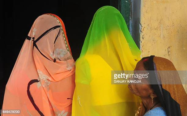 TOPSHOT Indian voters queue as they await their turn to cast their votes at a polling station in Varanasi on March 8 during the last phase of state...