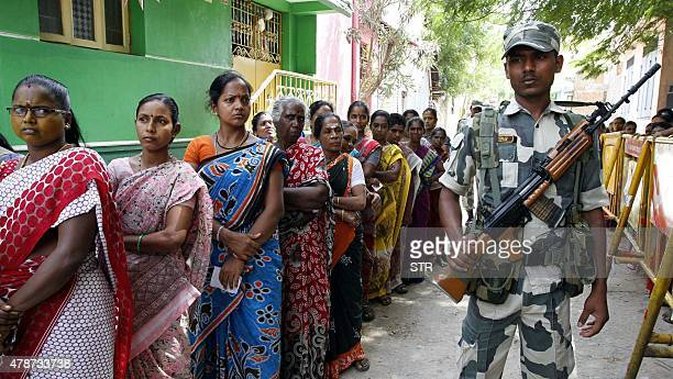 Indian voters queue as they wait to cast their ballot at a polling station during the byelection at R K Nagar in the southern city of Chennai on June...