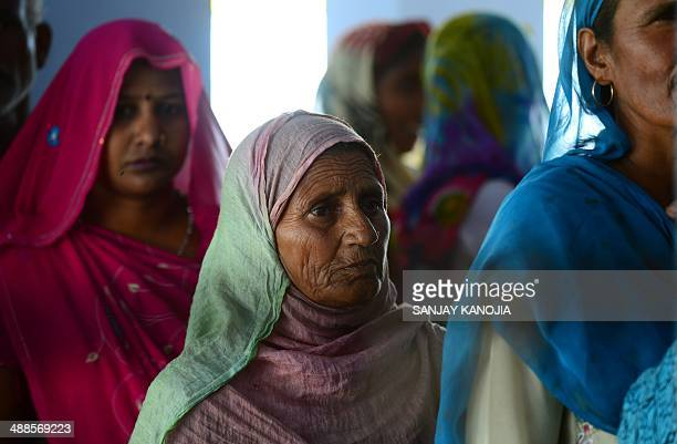 Indian voters queue at a polling station to cast their ballots during voting in Amethi on May 7 2014 More than 95 million voters are eligible to vote...