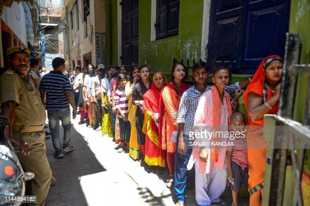 Indian voters queue at a polling station to cast their votes in Varanasi in Uttar Pradesh state on May 19 during the 7th and final phase of India's...