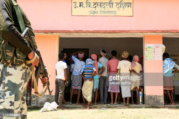 TOPSHOT Indian voters queue to cast their votes as a CRPF personnel stands guard at Shikaripara area in the Dumka district of Jharkhand state on May...