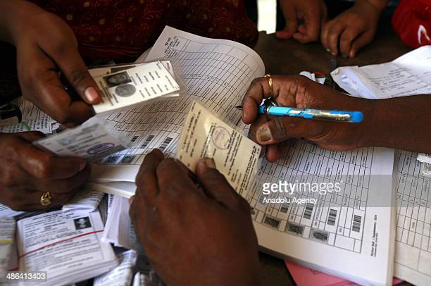 Indian voters show their voter identification papers to election commission officials before casting their ballots during the sixth phase of the...