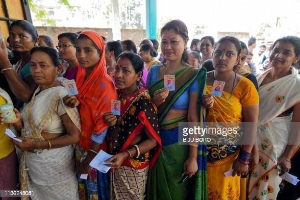 Indian voters show their voter identity cards as they stand in a queue to cast their vote at a polling station during India's general election in...