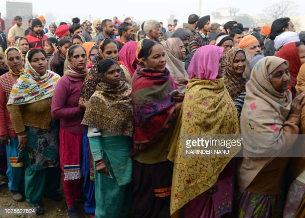 Indian voters stand in line to cast their votes for Punjab local election at a polling station in a village on the outskirts of Amritsar on December...