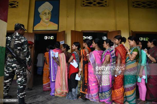 TOPSHOT Indian voters stand in queue to cast their votes at a polling station as security personnel stand guard during India's general election in...