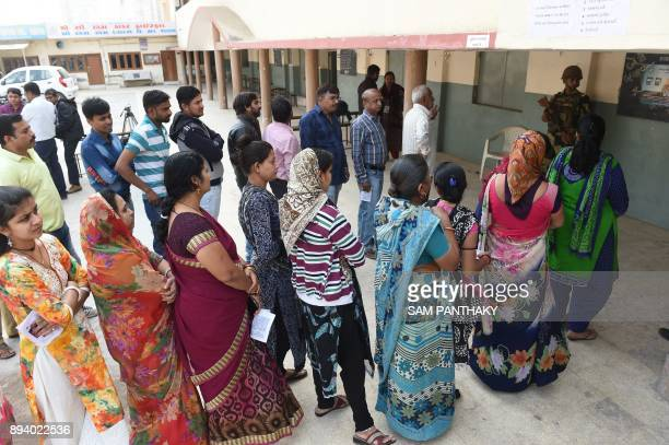 Indian voters wait for their turn to cast their votes in a repolling centre at Nava Naroda on the outskirts of Ahmedabad on December 17 2017 Voting...