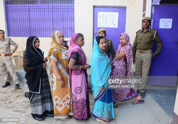 Indian voters wait to cast their ballots during a by-election for the Phulpur Lok Sabha seat on the outskirts of Allahabad on March 11, 2018. The...