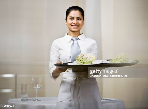 Indian waitress carrying tray of food