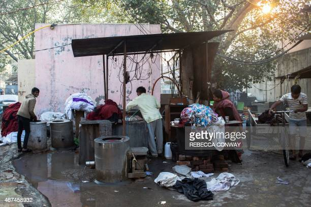 Indian washerman Om Prakash and his wife Sunita talk with their employees Rohit Kumar and Bula Kumar as they work to wash and dry towels used at a...