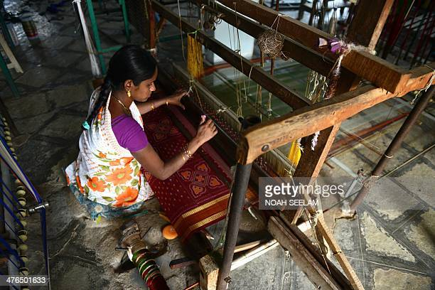 Indian weaver Bathila Archana weaves a silk saree on a handloom in a workshop at Bhoodan Pochampally in Nalgonda District some 55kms from Hyderabad...