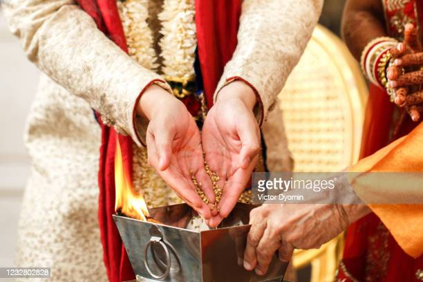 indian wedding traditions. bride and groom pour rice into the fire - gold medal stock pictures, royalty-free photos & images
