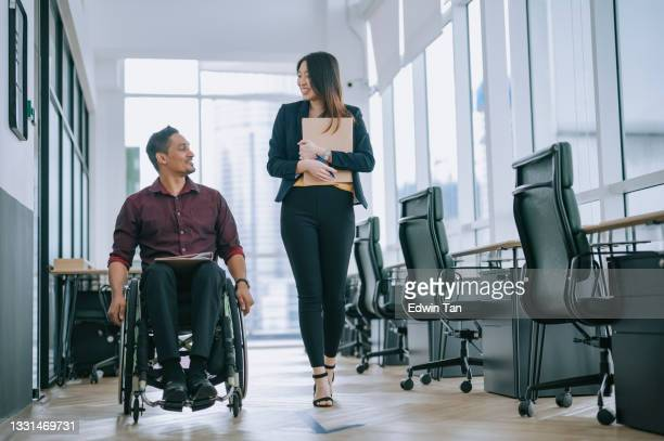 indian white collar male worker in wheelchair having cheerful discussion conversation with his female asain chinese colleague coworking at walkway corridor - employee stock pictures, royalty-free photos & images