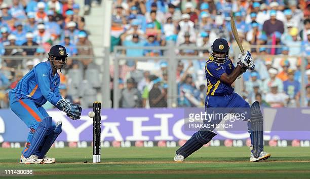 Indian wicketkeeper captain Mahendra Singh Dhoni watches as Sri Lankan batsman Mahela Jayawardene plays a shot during the ICC Cricket world Cup final...