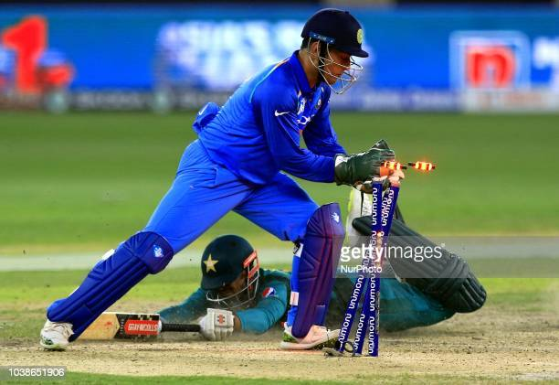 Indian wicketkeeper MS Dhoni removes the bails as Pakistan cricketer Shadab Khan dives in to complete a run during the Asia Cup 2018 cricket match...