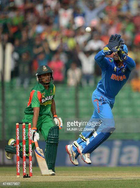 Indian wicketkeeper Dinesh Karthik attempts to catch the ball as Bangladesh cricketer Anamul Haque makes ground during the second match of the Asia...