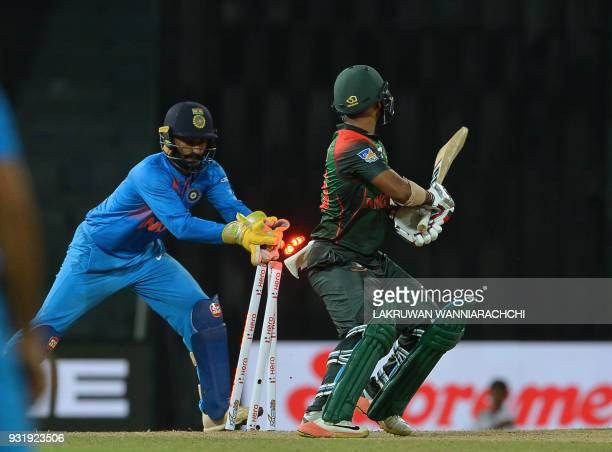 Indian wicketkeeper Dinesh Karthik attempts to stump Bangladesh cricketer Liton Das during the fifth Twenty20 international cricket match between...
