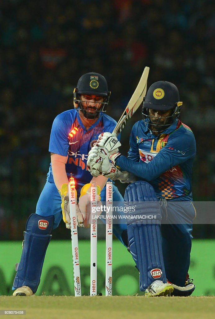 Indian wicketkeeper Dinesh Karthik (L) looks on as Sri Lankan batsman Upul Tharanga (R) is dismissed by Indian bowler Yuzvendra Chahal during the opening Twenty20 international cricket match between Sri Lanka and India for the Nidahas Trophy tri-nation Twenty20 tournament at The R. Premadasa Stadium in Colombo on March 6, 2018. The Nidahas Trophy tri-nation Twenty20 tournament involving Sri Lanka, Bangladesh and India. /