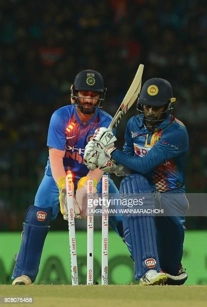 Indian wicketkeeper Dinesh Karthik looks on as Sri Lankan batsman Upul Tharanga is dismissed by Indian bowler Yuzvendra Chahal during the opening...