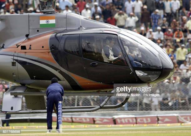 Indian wicketkeeper Mahendra Dhoni sits in the front seat of an Indian military helicopter as it attempts to dry the outfield at the Nehru Stadium...