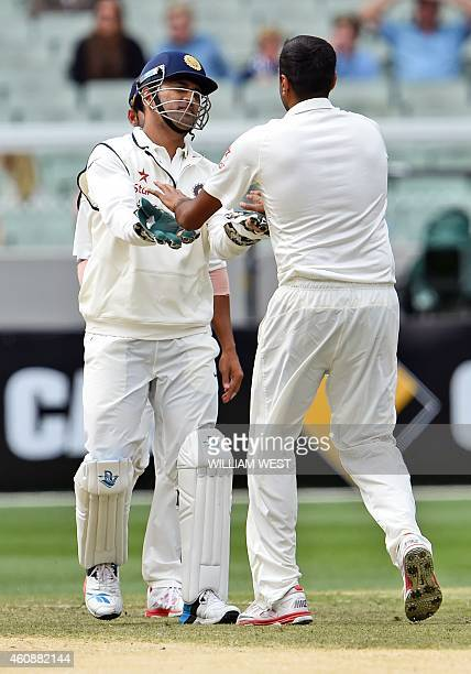 Indian wicketkeeper Mahendra Singh Dhoni congratulates spinner Ravi Ashwin after dismissing Australian batsman Chris Rogers during the fourth day of...