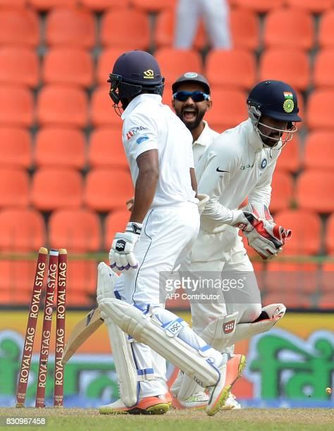 Indian wicketkeeper Wriddhiman Saha and teammate Ajinkya Rahane celebrate after he dismissed Sri Lankan cricketer Niroshan Dickwella during the...